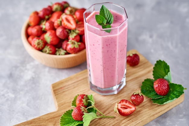 Smoothie with summer strawberry in glass jar and fresh berries