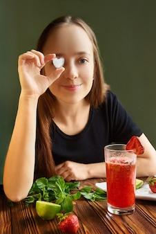 Улыбающаяся девочка держит лед в форме сердца. женщина рука коктейль коктейль. усмехаясь девушка счастливая дома и выпивая красный здоровый smoothie на кухне.