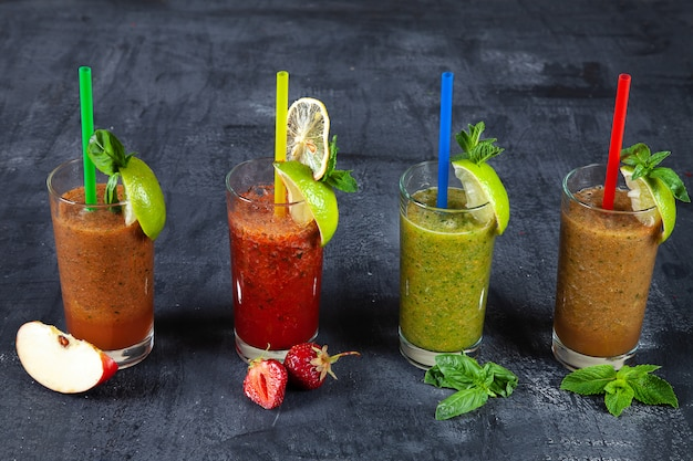 Закройте вверх по взгляду на различном комплекте smoothie на темной предпосылке. здоровые свежие фруктовые и овощные коктейли с различными ингредиентами в стекле.