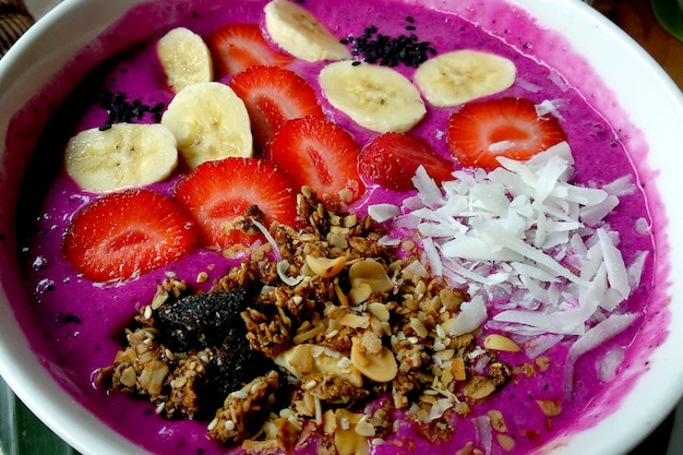 Smoothies bowl with banana, granola, and strawberry