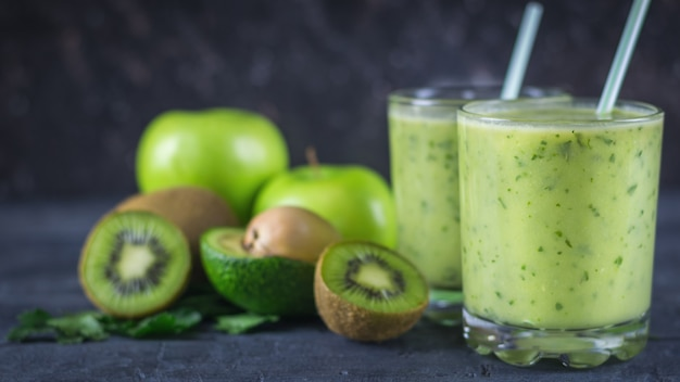 Smoothies from avocados, bananas, kiwi and herbs on a dark wooden table. diet vegetarian food.