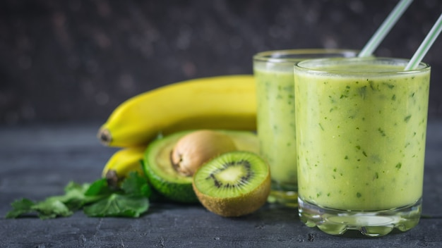 Smoothies from avocados, bananas, kiwi and herbs on a wooden table. diet vegetarian food.