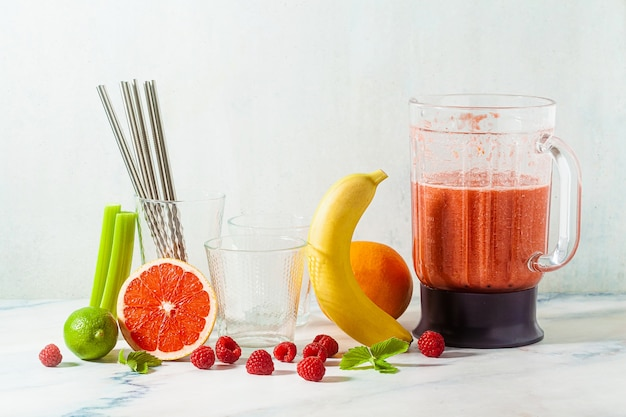 Smoothies in a glass blender bowl and ingredients on the table. not disposable metal tubes. healthly food.