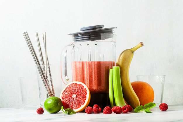 Smoothies in a glass blender bowl and ingredients on the table.