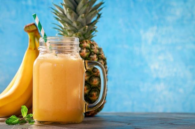 コピースペースのあるガラス瓶に入ったパイナップルバナナとオレンジのスムージー
