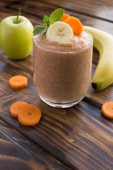 茶色の木製の背景のガラスにバナナ、リンゴ、ニンジンのスムージーまたはピューレ