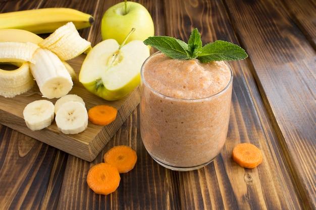 Смузи или пюре с бананом, яблоком, морковью и ингредиентами на коричневой деревянной поверхности