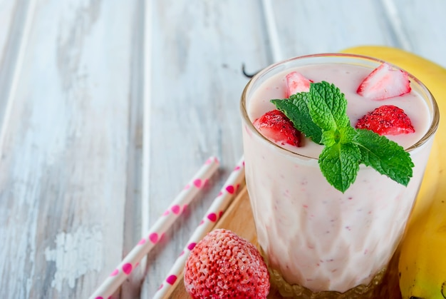Smoothies of strawberries and banana in glasses and ingredients on a wooden table