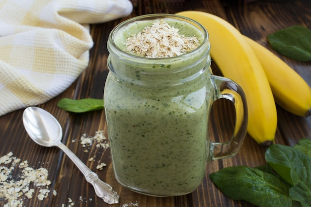 Smoothies with banana, spinach and oat flakes  on the brown wooden background