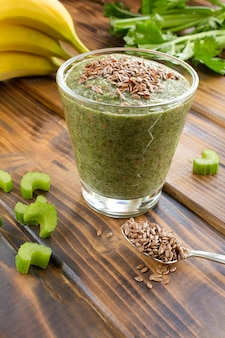 Smoothies with flax seeds, celery and banana  in the glass on the brown wooden surface. location vertical.