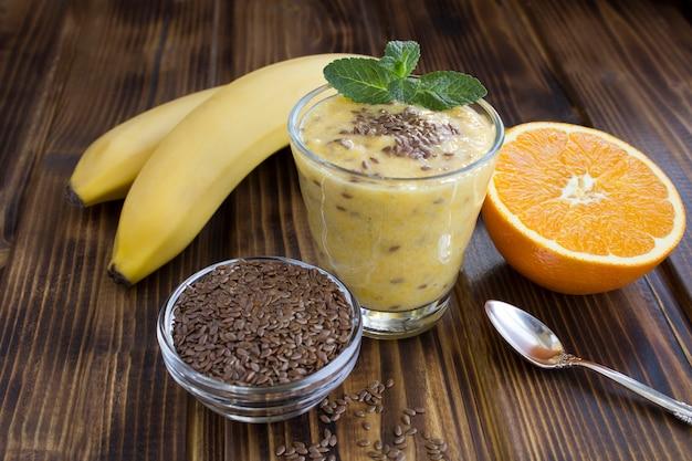 Смузи с семенами льна, апельсин и банан в стакане на коричневой деревянной поверхности. крупный план.