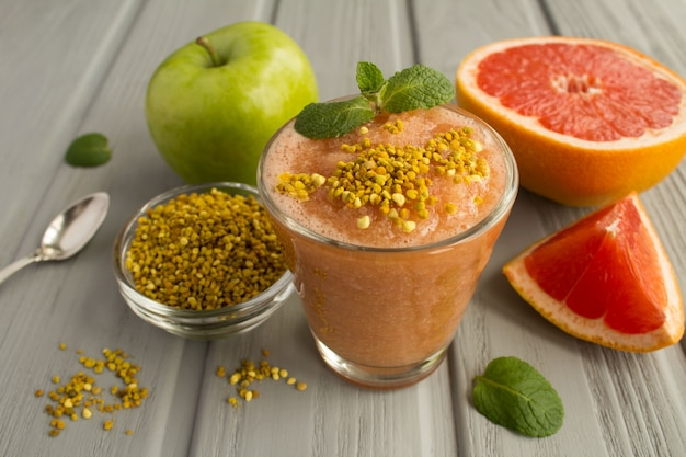 Smoothies with grapefruit, green apple and  bee pollen on the grey wooden background