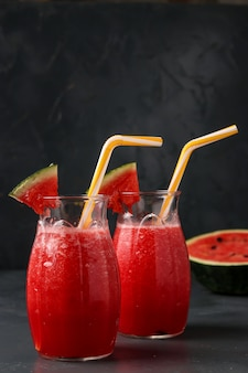 Smoothies with watermelon in jars on a dark surface, vertical orientation