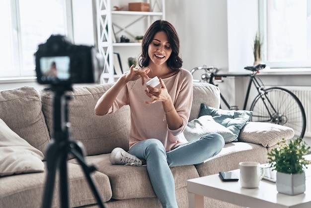 スムージングクリームレビュー。ソーシャルメディアビデオを作成しながら美容製品をテストし、笑顔の美しい若い女性