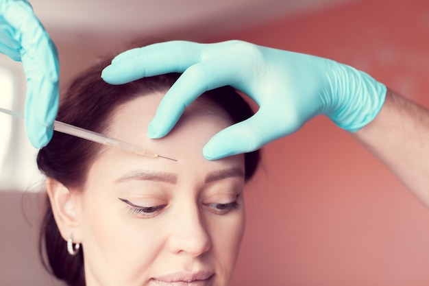 Smoothing facial wrinkles on a forehead with botox injections