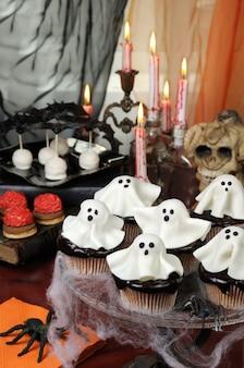 Торты шведского стола в шоколадной глазури украшают марципановые привидения на хэллоуин