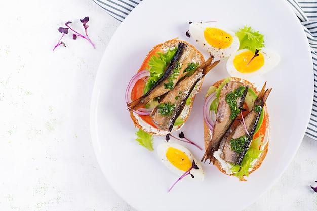 Сморреброд со шпротами, авокадо, помидорами, яйцом и сливочным сыром на белой тарелке