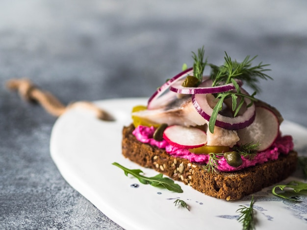伝統的なデンマークオープンサンドイッチ -  smorrebrod。ニシンのスライスと野菜の濃いライ麦パン。