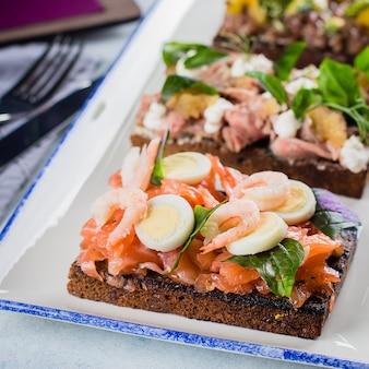 スカンジナビアの軽食。 smorrebrods伝統的なデンマークオープンサンドイッチ、濃いライ麦パン