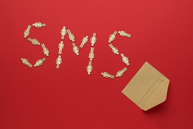 Sms inscription made of wooden men and an open postal paper envelope on a red background. the concept of communication between people.