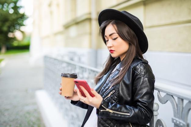 Молодое азиатское чтение женщины используя новости чтения телефона или отправляя смс sms на smartphone пока выпивающ кофе на проломе от работы.