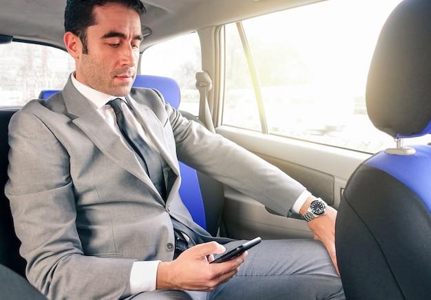 スマートフォンでテキストメッセージのsmsながらタクシーに座っている若いハンサムな実業家
