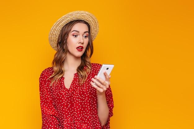 Удивленная девушка-модель в красном платье с красной помадой и соломенной шляпкой держит мобильный телефон и читает sms-сообщение, делает онлайн покупки изолированными на оранжевой стене. летняя девушка с клеткой