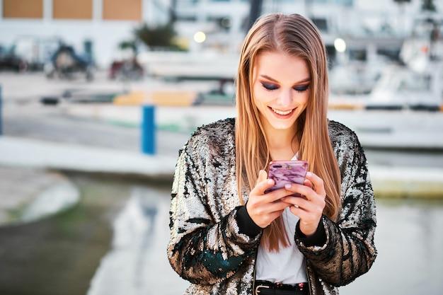 幸せな美しいブロンドの女性が歩いて、smsメッセージを書く