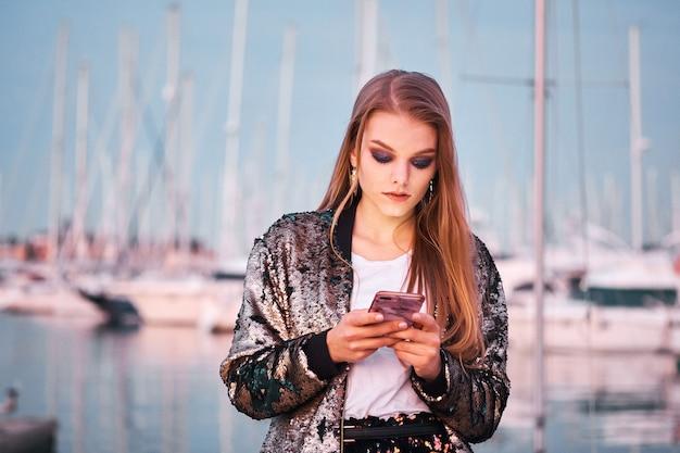 歩くとsmsメッセージを書く若い美しいブロンドの女性