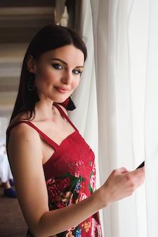 Молодая красивая женщина пишет sms на свой мобильный телефон.