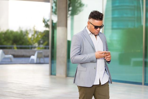 Серьезный бизнесмен, отвечающий на sms на смартфоне