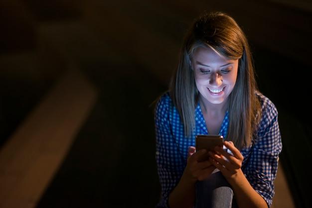 Возбужденная красивая девушка получает сообщение sms с хорошей новостью в мобильном телефоне за пределами