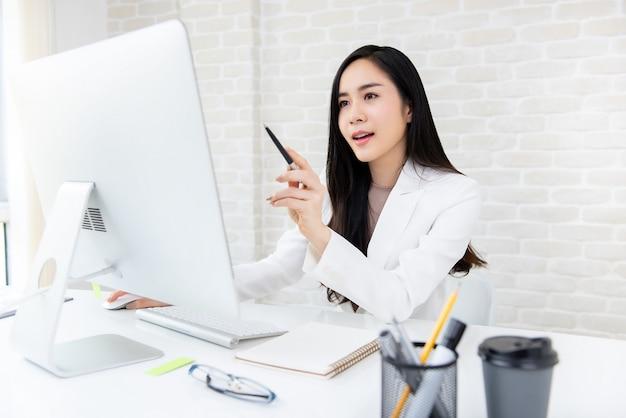 Smsart красивая азиатская коммерсантка работая на компьютере в офисе