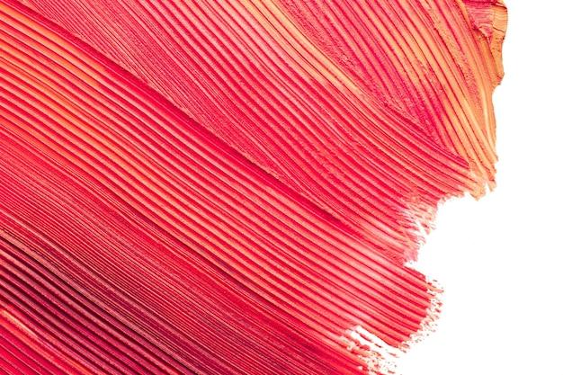 Smudged red orange matte lipstick texture on white background