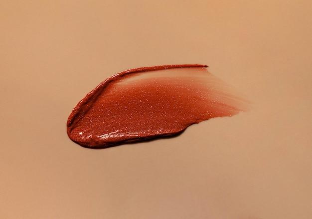 Размытая текстура коричневой мерцающей помады на бежевом фоне