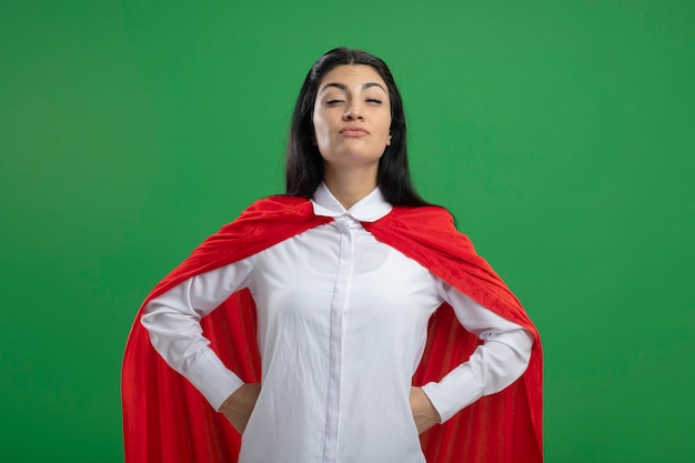 Самодовольная молодая кавказская девушка-супергерой держится за руки на бедрах с наполовину закрытыми глазами, глядя в камеру, изолированную на зеленом фоне с копией пространства