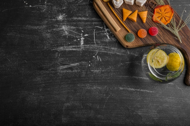 Закусочная и кондитерская доска с картофелем в воде на черном фоне, вид сверху