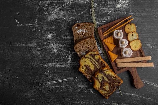 Закусочная и кондитерская доска с нарезанным тортом