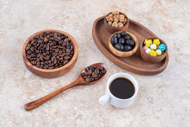 コーヒー豆と淹れたてのコーヒーの横にある木製トレイのスナックの品揃え