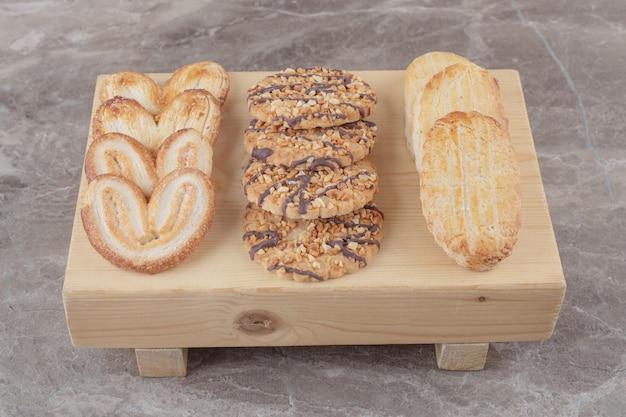 Assortimento di snack con biscotti diversi su una piccola tavola su marmo