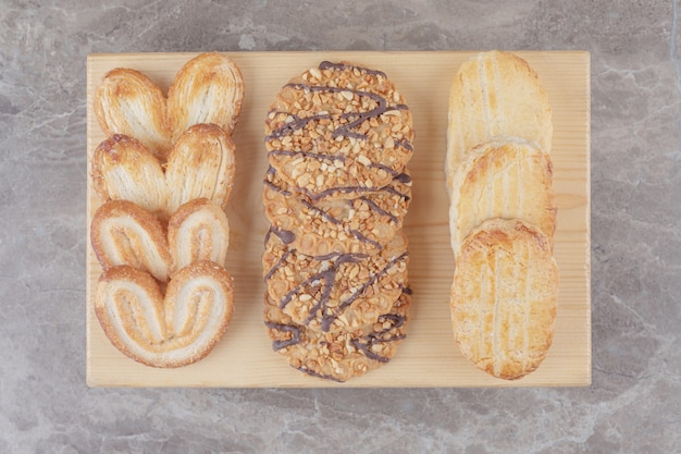 Snack assortment with different cookies on a small board on marble