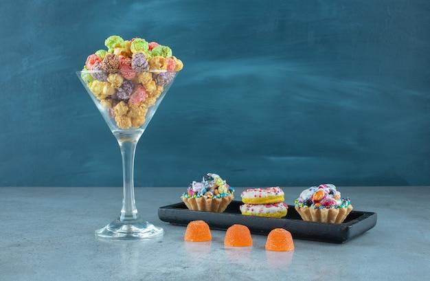 대리석 표면에 도넛, 팝콘, 컵 케이크 및 젤리 캔디로 구성된 스낵 구색