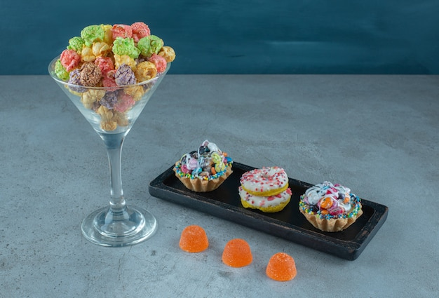 Snack assortment with donuts, popcorns, cupcakes and jelly candies on marble surface