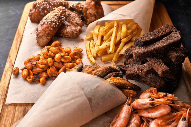 Snack to beer, on a wooden board. shrimp. fried fish. fried peanuts. fries. chicken wings.crunches. croutons.