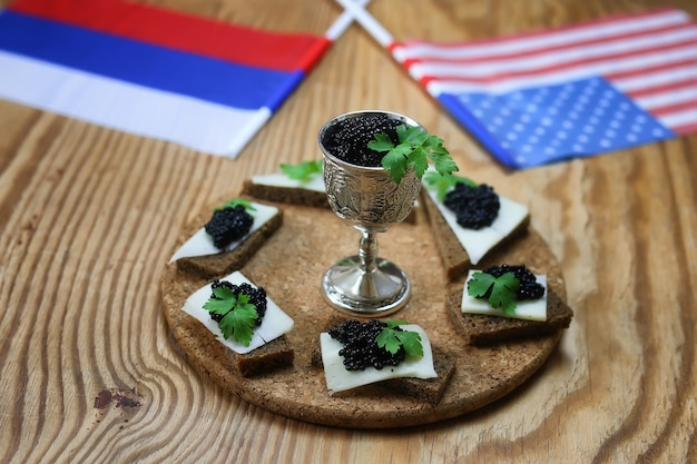 Snack black caviar on a wooden background