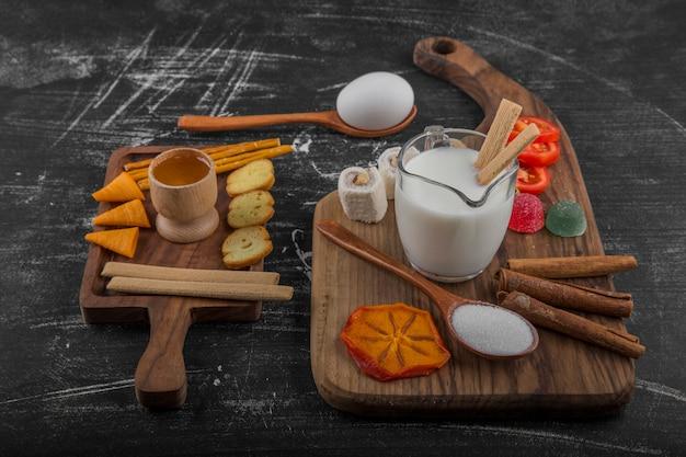 Spuntino con patatine, cracker e pasticcini sul piatto di legno, vista angolare