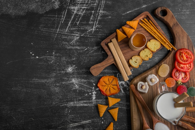 Snack board with chips, crackers and pastries on the wooden platter