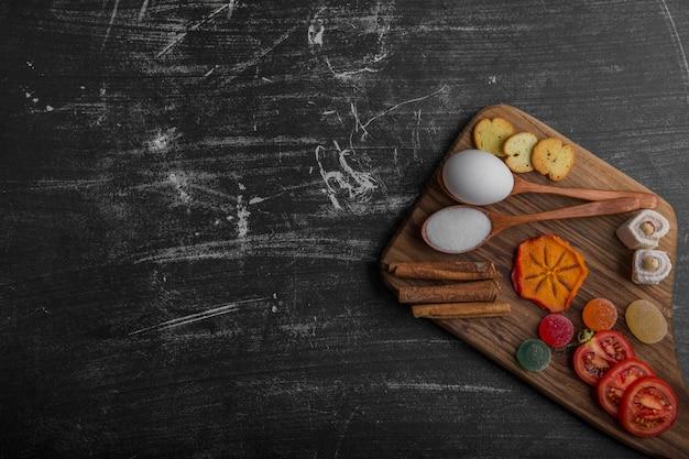 Spuntino con patatine, cracker e pasticcini sul piatto di legno