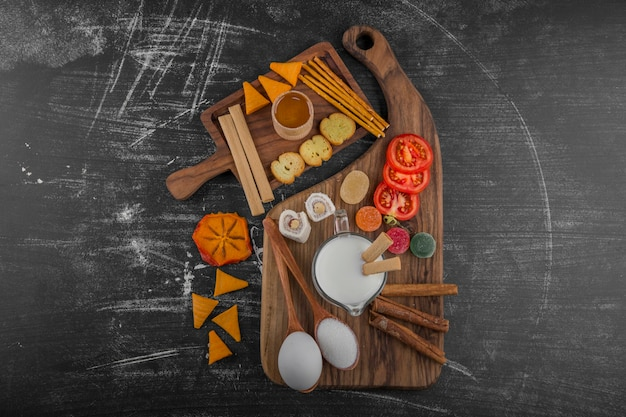 Snack board with crackers and vegetables isolated on black