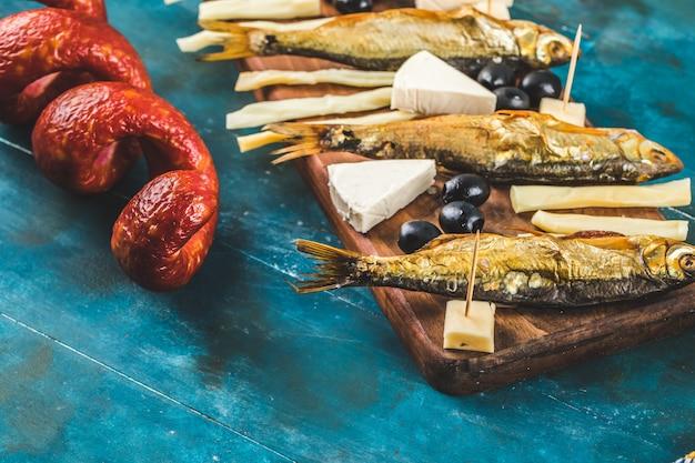 Снэк доска с ломтиками колбасы, кубиками сыра и маслинами с крекерами и сухой рыбой на синем столе